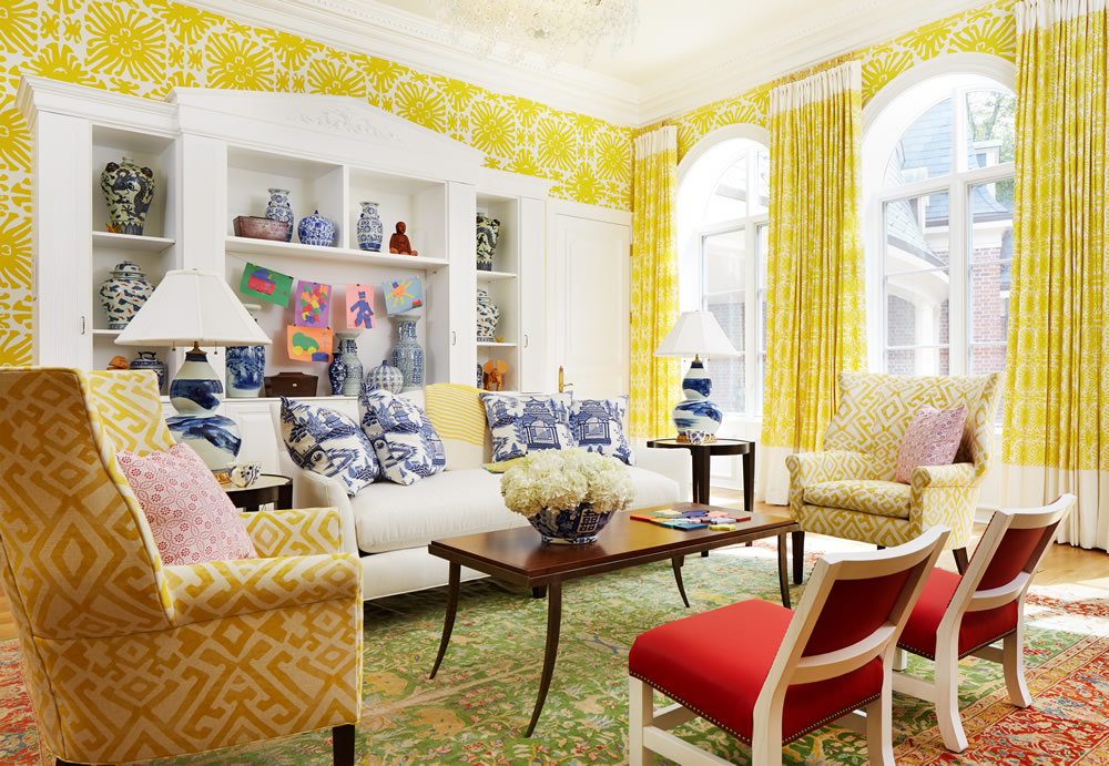 Quadrille wallpaper in living room with red chairs.